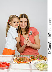 Daughter hugging her mother six years, which is preparing a pizza
