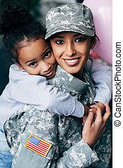 daughter hugging mother in military uniform