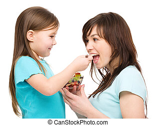 Daughter is feeding her mother with fruit salad