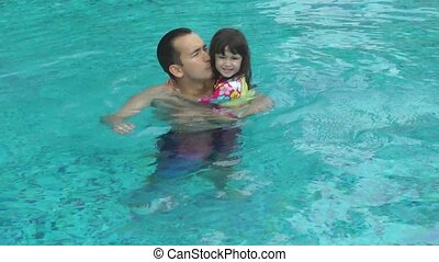 Daughter kisses her father in the pool