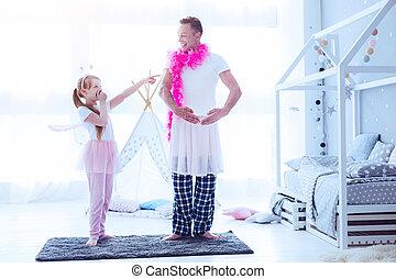 Daughter laughing at dad pretending to be ballerina