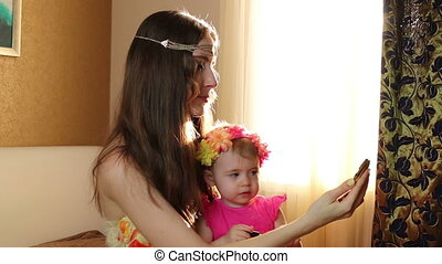 Daughter makes up lips with lipstick to the mom. Mother plays with her daughter in the nursery near the window.