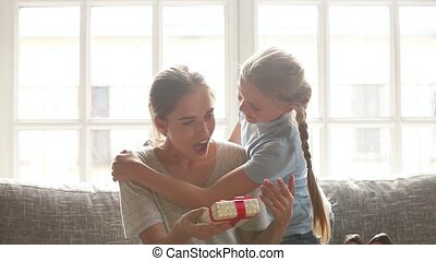 Daughter making surprise to happy mom congratulating with...