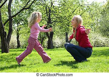 daughter runs to mother in spring park