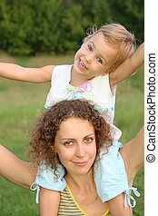 daughter sits on the shoulders in mother