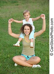daughter sits on the shoulders in mother on to the meadow