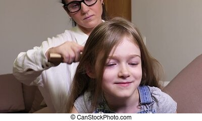 Daughter start smiling when mother combing her hair