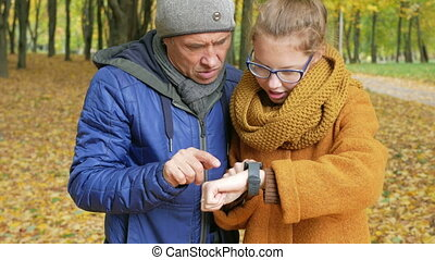 Daughter teenager teaches his father to work with the smart watch in the autumn park. Dad listens carefully and repeats the daughter of her touch display