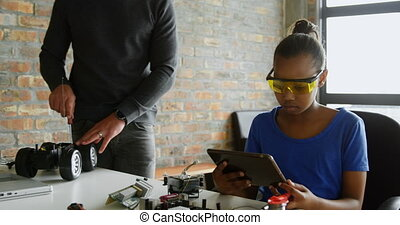 Daughter using digital tablet while father repairing electric car 4k