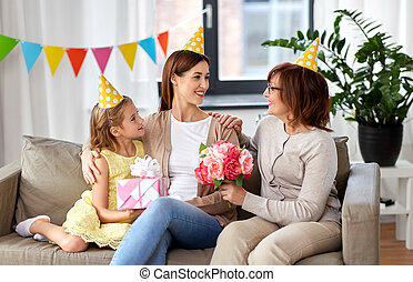 daughter with gift box greeting mother on birthday