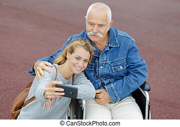daughter with her disabled father in wheelchair doing a selfie