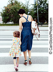 Daughter with her mother crossing the road
