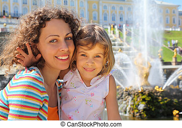 Daughter with mother  near fountains of Petergof, Saint Petersburg, Russia