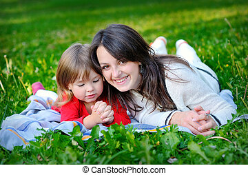 daughter with mother on grass