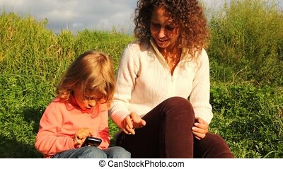 daughter with mother play in communicator in park in summer