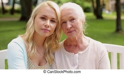 daughter with senior mother sitting on park bench - family,...