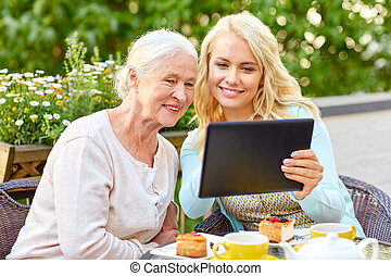 daughter with tablet pc and senior mother at cafe