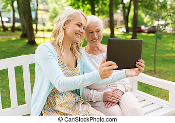 daughter with tablet pc and senior mother at park