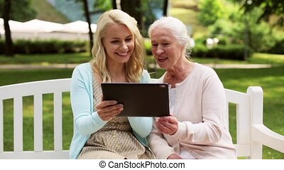 daughter with tablet pc and senior mother at park - family,...