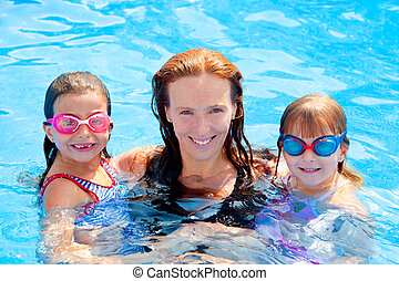 daughters and mother family swimming in pool on summer ...