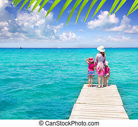 Daughters and mother in jetty on tropical beach