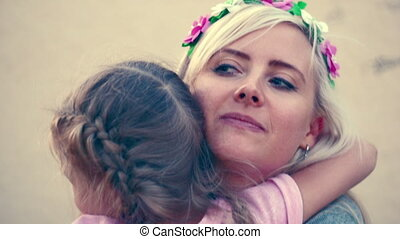 Daughters rush into the arms of the mother on the street and tightly embrace her and press her to it with all the love.