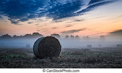 Dawn at foggy valley in autumn with hay on field