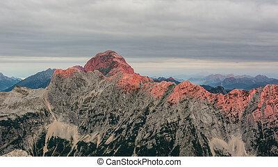Dawn illuminating mountain ridge. Mangart and Ponce,...