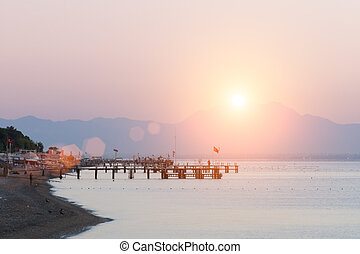 Dawn on the sea beach. Pier. The mountains in the morning mist are far away.