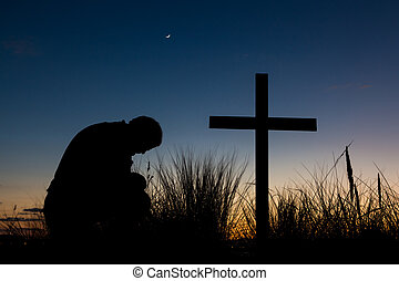 Dawn Prayer - Man praying as a start of a new day begins to...