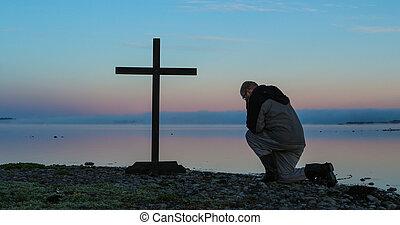 Dawn Praying Man - Man kneeling in pray before a cross, with...
