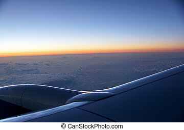 Sunrise light over the world full of clouds with Airplane Jet Wing