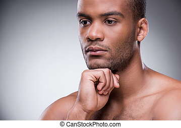 Day dreamer. Portrait of young African man holding hand on chin and looking away while standing against black background