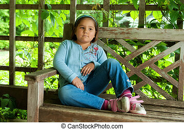 Day Dreaming - A little girl sitting on a park bench is day ...