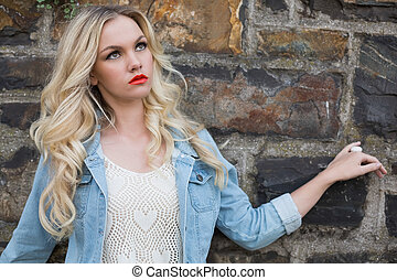 Day dreaming casual blonde wearing denim clothes posing ...