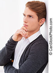 Day dreaming handsome. Side view of thoughtful young man holding hand on chin and looking away while leaning at the wall