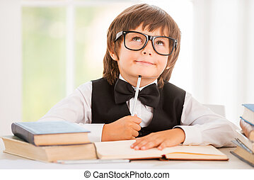 Day dreaming. Little boy leaning his face on pen and looking away while sitting at the desk