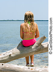 Day dreaming - Young girl daydreaming on driftwood at waters...