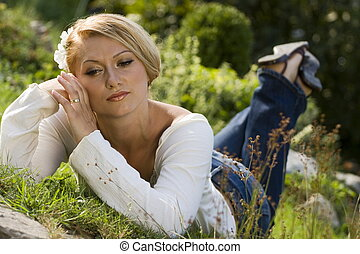 Day dreaming - Young woman lying in the grass on a hot ...