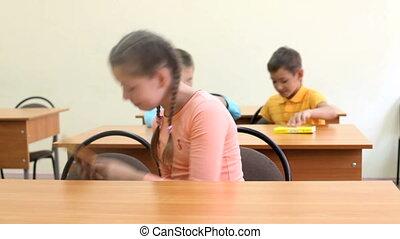Day in school  - Three children sitting at desks in school