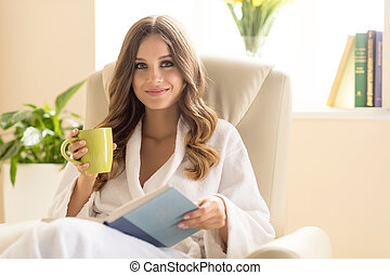Day off at home. Attractive young woman in bathrobe drinking...