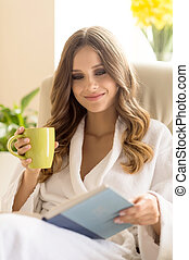 Day off at home. Beautiful young woman in bathrobe drinking coffee and reading book