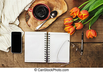 Overhead shot a bouquet of an open book, cell phone, coffee and flowers over a wood table top ready to plan an agenda. Flat lay top view style.