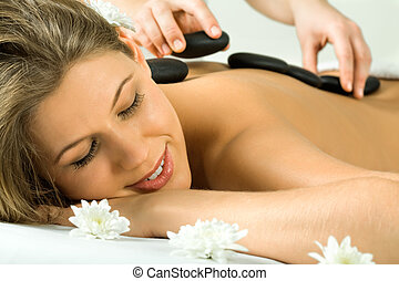 Day spa - Photo of therapist putting the hot stones on the...