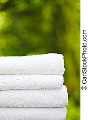 Day spa - Stack of fresh white towels in a garden setting...