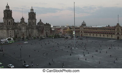 day to night time-lapse of the zocalo in mexico city, with the cathedral and giant flag pole in the centre