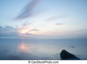 daybreak over a calm ocean with rock in the foreground