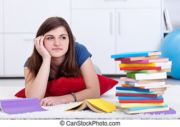 Daydreaming by the school books - pensive teenager girl at home