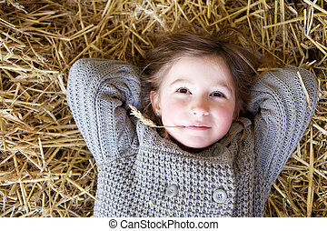 Close up portrait of a young girl lying down on hay and daydreaming