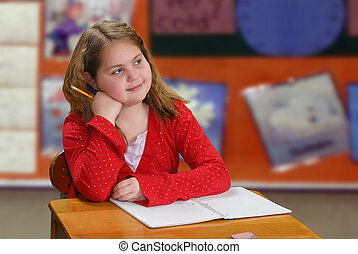Elementary age girl, with a smile, sitting at her desk thinking about what to write